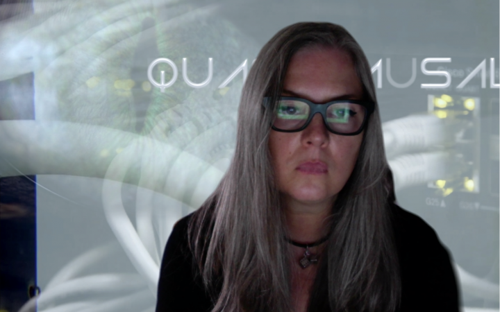 Ami Clarke, a woman with long hair and glasses with a thick, square frame, looks at a screen. This screen is reflected in her glasses.