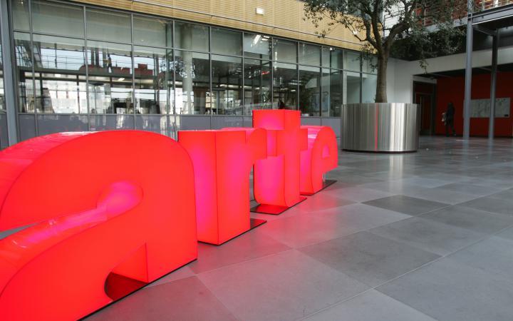 Das arte-Logo steht in leuchtendem Pink in einem gläsernen Atrium.