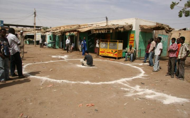 Artist Barış Seyitvan sits inside a white circle painted on the floor in a Sudanese village.