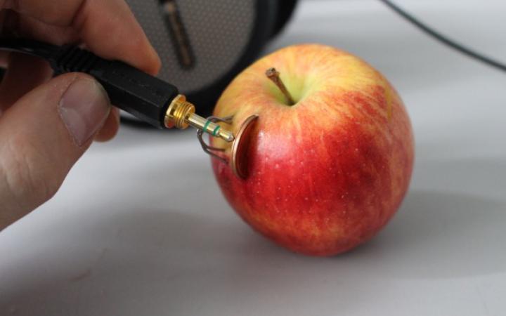 In einem Apfel stecken eine Kupfermünze und ein Zinkdraht, jemand hält an beide metallenen Gegenstände einen Klinkenstecker durch den nun Strom fließt.