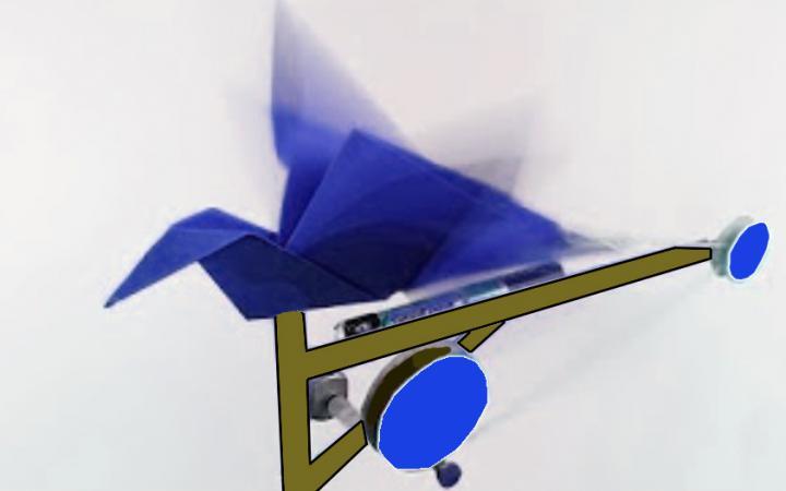 Ein aus blauem Papier gefalteter Origami-Vogel ist auf eine Unterkonstruktion mit Rädern geklebt. Außerdem ist eine Batterie an dem Objekt angeschlossen.