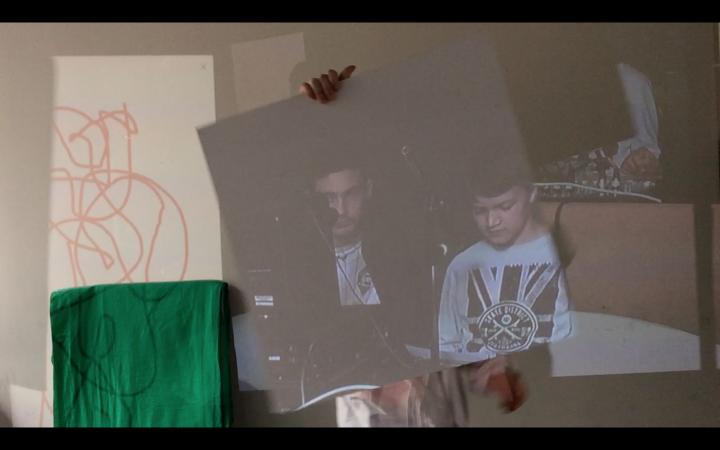 Ein Schüler hält ein Foto von zwei Schülern hoch im Rahmen der Veranstaltung »Global Sound«.