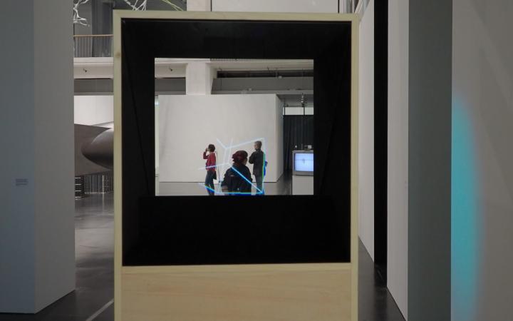 Blick durch einen Kasten mit einer durchsichtigen Platte in einen Raum. Im Raum ist eine animierte geometrische Figur zu sehen.