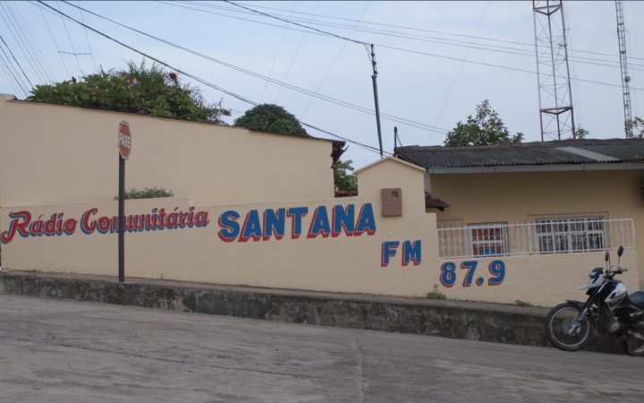 """Zu sehen ist eine Häuserwand auf der steht """"Radio Comunitaria Santana FM 87.9""""."""