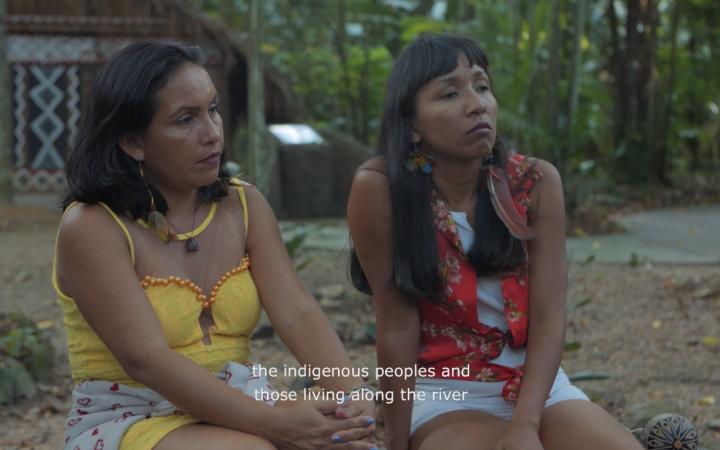 Zu sehen sind zwei Frauen, die interessiert jemandem außerhalb des Bildes zu hören. Um sie herum ist es grün und ländlich.
