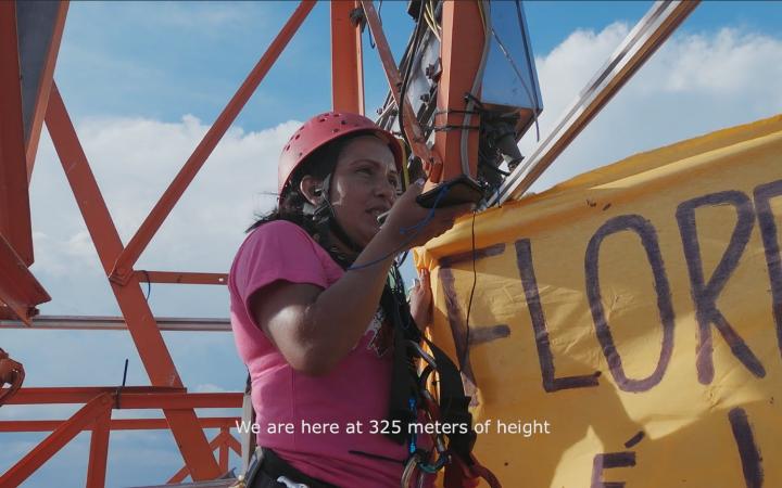 Zu sehen ist eine Frau auf einem Stahlgerüst, die in der einen Hand ein großes Banner und in der anderen Hand ein Smartphone hält, in das sie reinspricht. Zu lesen ist: we are at 325 meters of height.