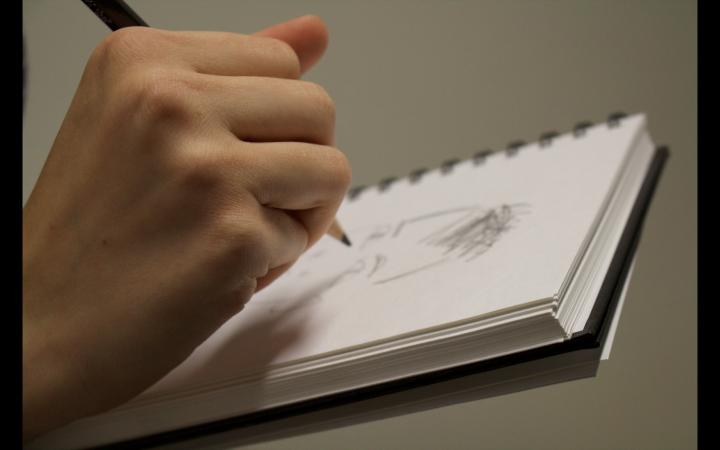 Eine Hand zeichnet etwas auf einem Block Papier.