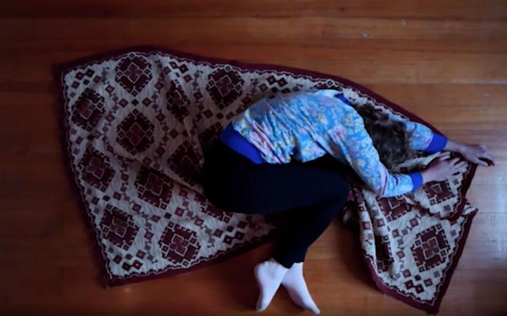 Das Bild zeigt eine Person, die auf einem Teppich liegt und sich darauf krümmt.