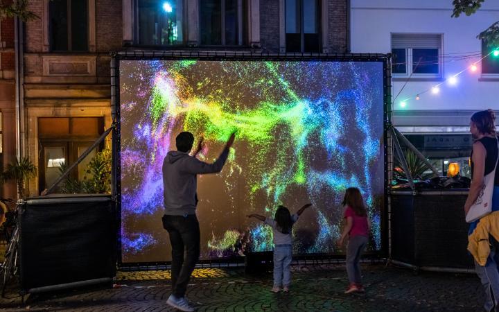 In der Fußgängerzone steht eine Leinwand mit leuchtend bunten Farbpartikeln, davor bewegen sich Erwachsene und Kinder.