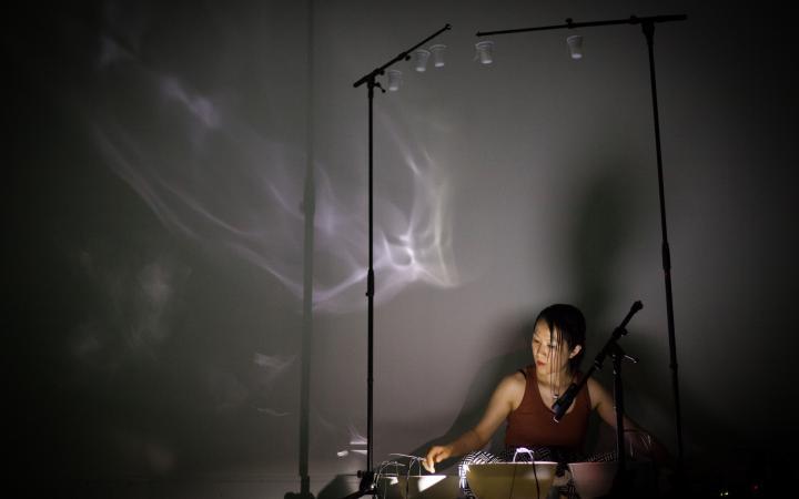 Tomoko Sauvage sitzt auf dem Boden, vor ihr stehen mit Wasser gefüllte Schalen. An der Wand sind Lichtreflexionen des Wassers zu sehen.