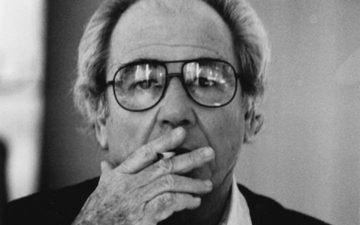 Schwarzweiße Fotografie: Jean Baudrillard, eine Zigarette rauchend.