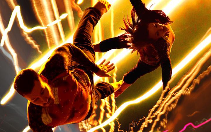 Das Bild zeigt zwei TänzerInnen, die aus einem Licht-Blitz-Gewitter herauszuschweben scheinen.