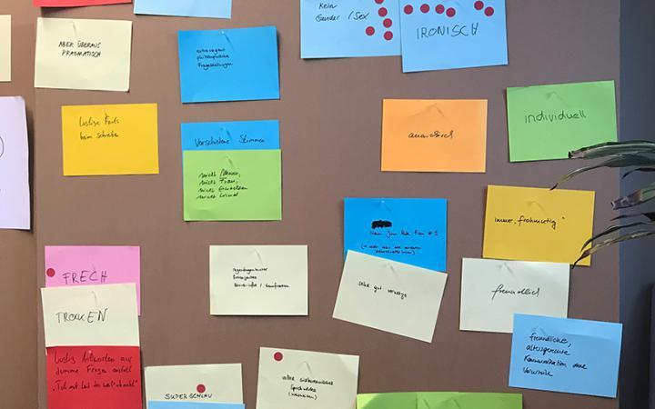 Zeichnungen mit möglichen Chatbot-Charakteren auf einer Pinnwand.