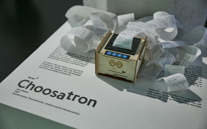 A wooden box with a printer, a four button interface and printed text on a roll