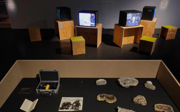 Foto aus der Ausstellung »Critical Zones« im Hintergrund laufen Videos auf Röhrenbildschirmen, im Vordergrund liegen Fotos und Gesteinsproben.