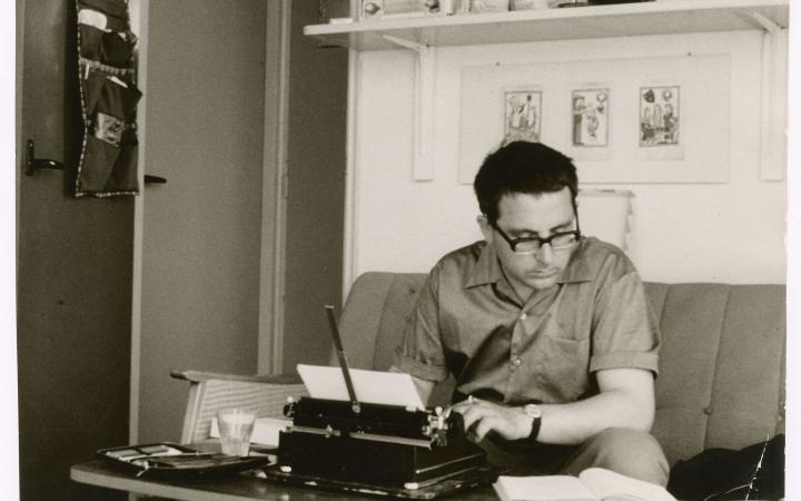 Theo Lutz sitz in einem Arbeitszimmer auf der Couch und arbeitet an der Schreibmaschine.