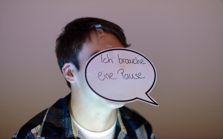 Ein Junge hat sich mit einer Sprechblase den Satz »ich brauche eine Pause« vor sein Gesicht geklebt.
