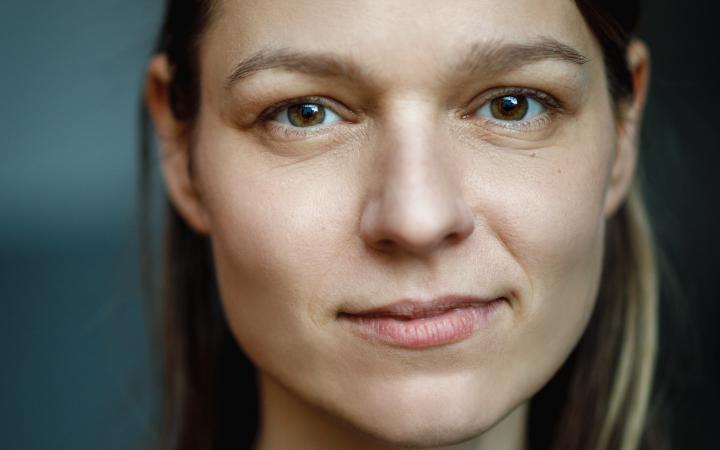 Ein Portraitfoto einer jungen Frau in Nahaufnahme. Sie hat lange Haare und scheut freundlich in die Kamera.