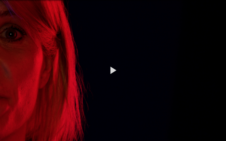 The left half of Dominika Szope's face illuminated in red against a black background.