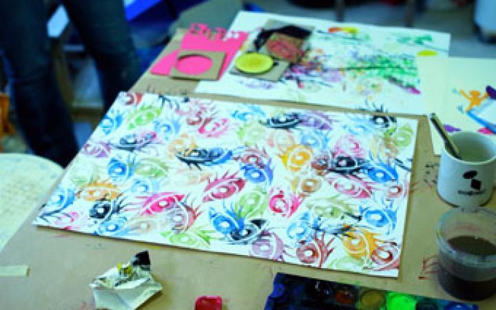 Ein mit bunten Augen bedrucktes Blatt Papier liegt auf dem Tisch mit allerlei Malutensilien darum.