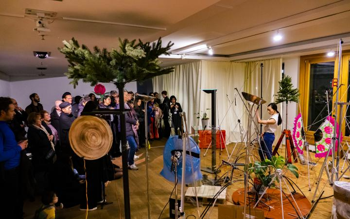 The cultural space Korea can be seen in Berlin during a performance. On the left side the visitors are standing while on the right side a performer moves between different sound objects.