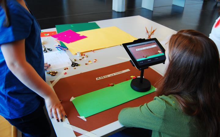 Zwei Mädchen arbeiten an einem Legetrickfilm, den sie mit dem iPad und einem Stativ Bild für Bild fotografieren.