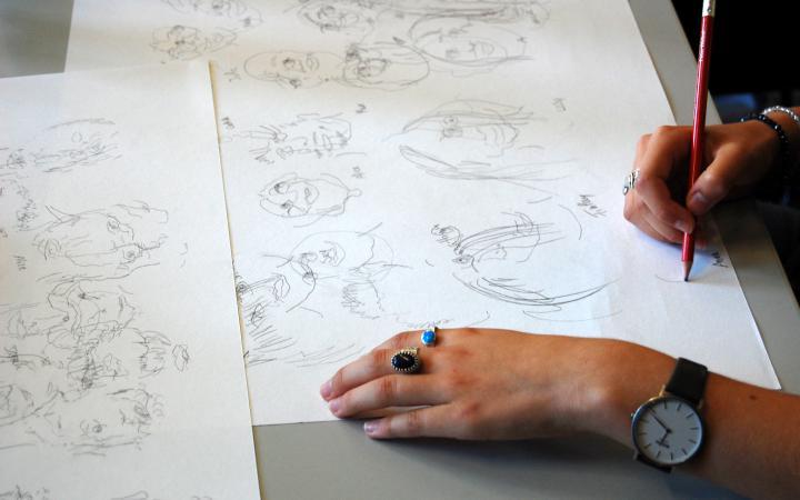 Zu sehen zwei Hände, die auf einem Blatt Papier zeichnen im Rahmen einer Veranstaltung der Kulturakademie.