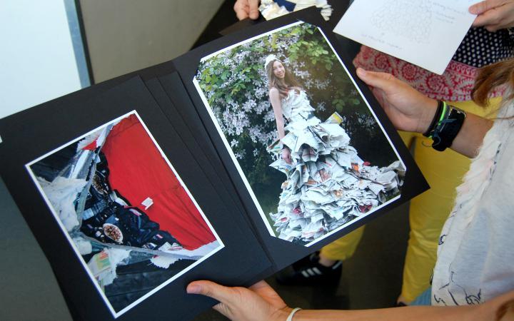 Eine junge Schülerin präsentiert ihre eingerahmten Fotografien im Rahmen einer Veranstaltung der Kulturakademie.