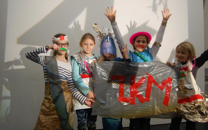 A group of girls dressed in clothes out of ordinary items are holding a banner, that has ZKM written on it with red tape.