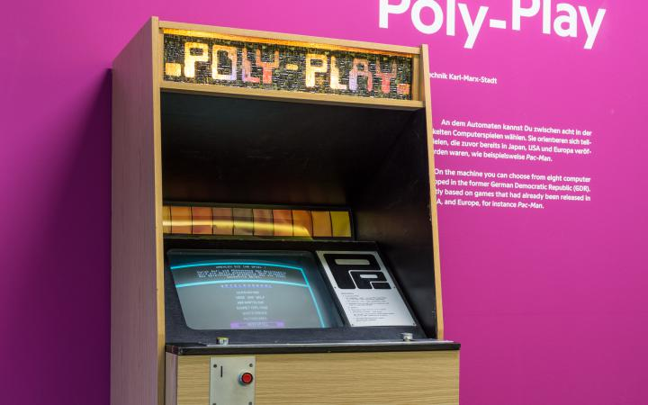A arcade cabinet in front of a violet wall