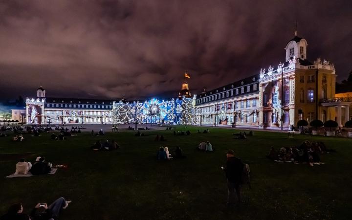 Foto eines bunten Projection Mappings bei Nacht auf dem barocken Karlsruher Schloss.