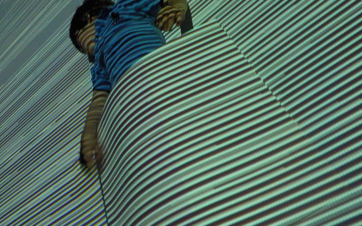 A boy in front of a wall with projections. In front of him there is a big piece of paper and it seams as though the boy is tucked into the projection.
