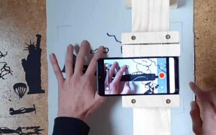 Das Bild zeigt als Nahaufnahme eine Hand, verschiedene Materialien und Schablonen sowie ein Mobilgerät. Das Bild ist im Rahmen der Kulturakademie Baden-Württemberg 2020/21 entstanden.