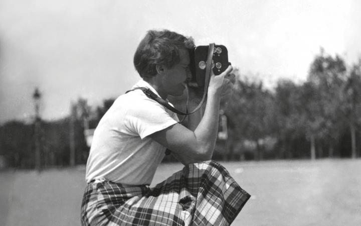 Die Schwarz-Weiß-Fotografie zeigt eine Frau in der Hocke mit einer Kamera.
