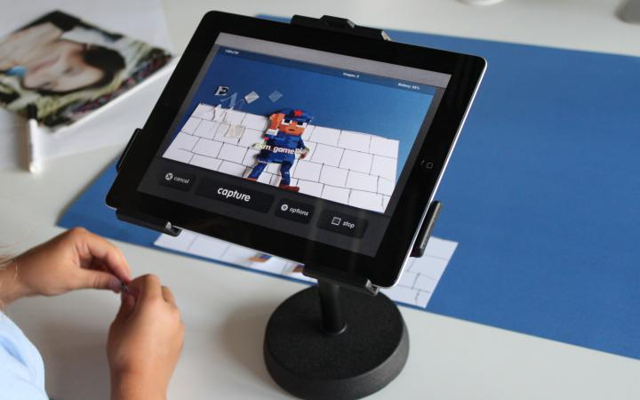 Man sieht zwei Kinderhände, die an einer Papiercollage arbeiten, die mit dem iPad zum Stop-Motion-Trickfilm wird.