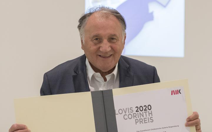 Ein Foto des Künstlers, Kurators und ZKM-Vorstands Peter Weibel, der den Lovis-Corinth Preis in Form einer Urkunde in den Händen hält.