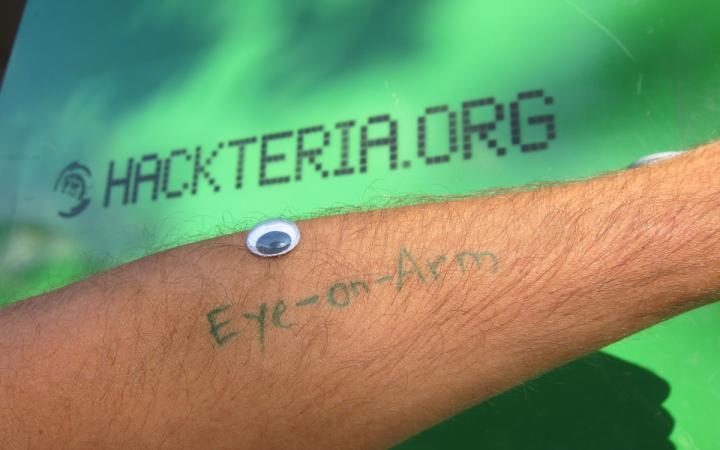 Auf einem Männerarm ist mit grüner Schrift Eye-on-Arm geschrieben und ein Spielzeugauge liegt darüber auf dem Unterarm. Der Hintergrund ist grün und mit der url hackteria.org beschrieben.