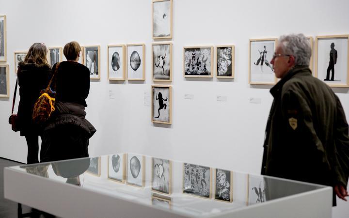 Zwei Frauen und ein Mann gehen an Wänden mit Bildern vorbei
