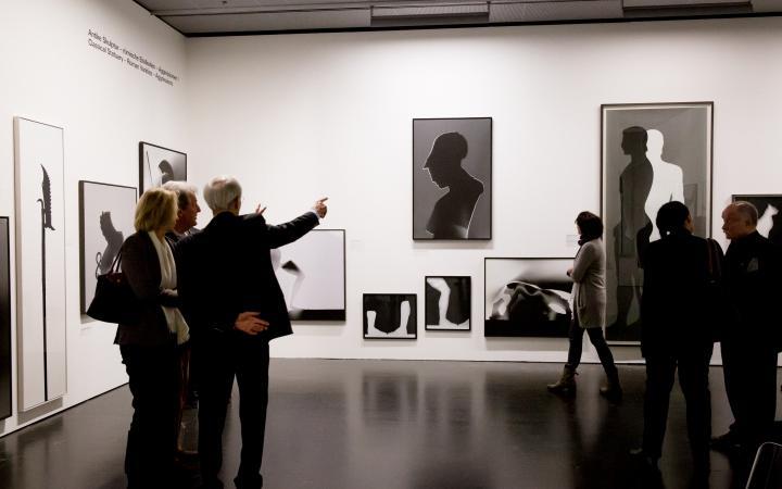 Mehrere Menschen laufen durch die Ausstellung »Leibniz' Lager«