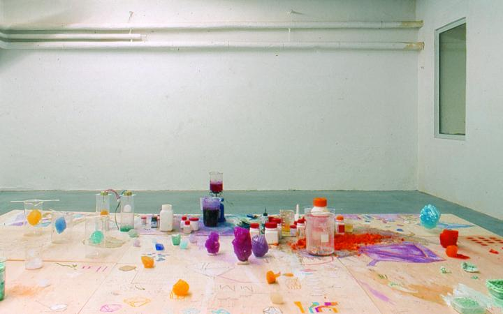 """View of the exhibition """"Fiction & Science». In the foreground a table with colorful crystals and chemicals."""