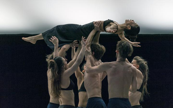Six dancers hold a dancer above their heads. The dancers are topless and wear dark trousers.
