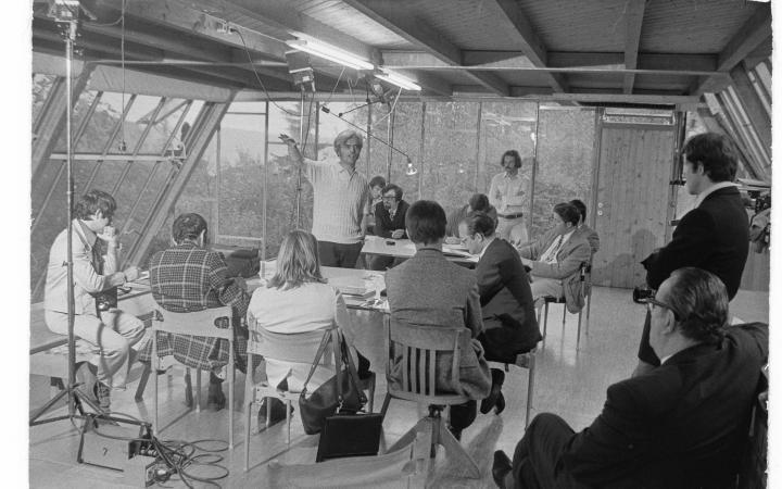 Eine alte schwarz-weiß Aufnahme des Architekten Frei Otto, der in einem Kreis von Zuhörern steht
