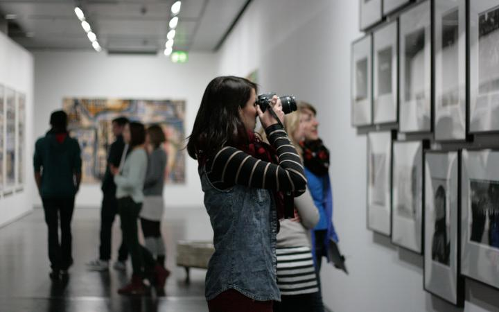 A woman is standing in the museum in front of numerous pictures on the wall. She is holding her camera and is making a picture from the pictures.