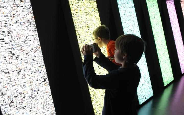 Two kids are standing in front of an illuminated wall. One of them is taking a photo of the installation and the other has his face very close to the work of art to look closely at the little pictures, that are beeing illuminated.