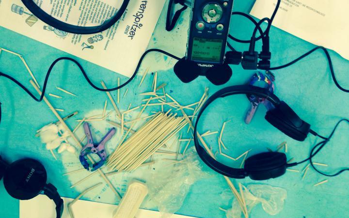 Ein Fieldrecorder, Kopfhörer, Holzstäbe, Papier und eine Zange liegen auf türkisem Untergrund.