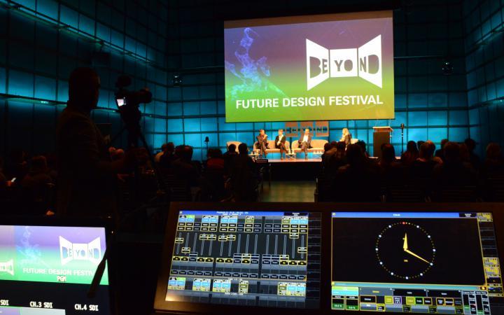 Blick in einen großen abgedunkelten Raum. An der gegenüberliegenden Wand ist eine große Leinwand mit dem Logo des Beyond Future Design Festivals zu sehen.
