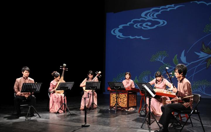 Six musicians in traditional Chinese clothing with their instruments on stage