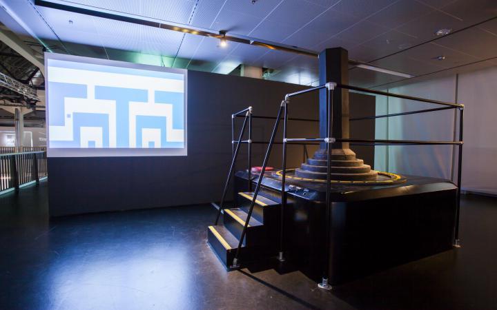 An oversized joystick an a screen showing a game