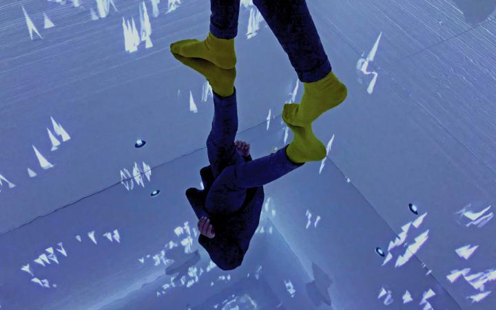 Füße in gelben Socken spiegeln sich auf einer verspiegelten Bodenplatte