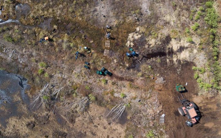 Eine Dronenaufnahme von oben, die auf eine Moorlandschaft blickt. Auf ihr arbeiten Menschen mit Müllsäcken, Baggern und Paletten.